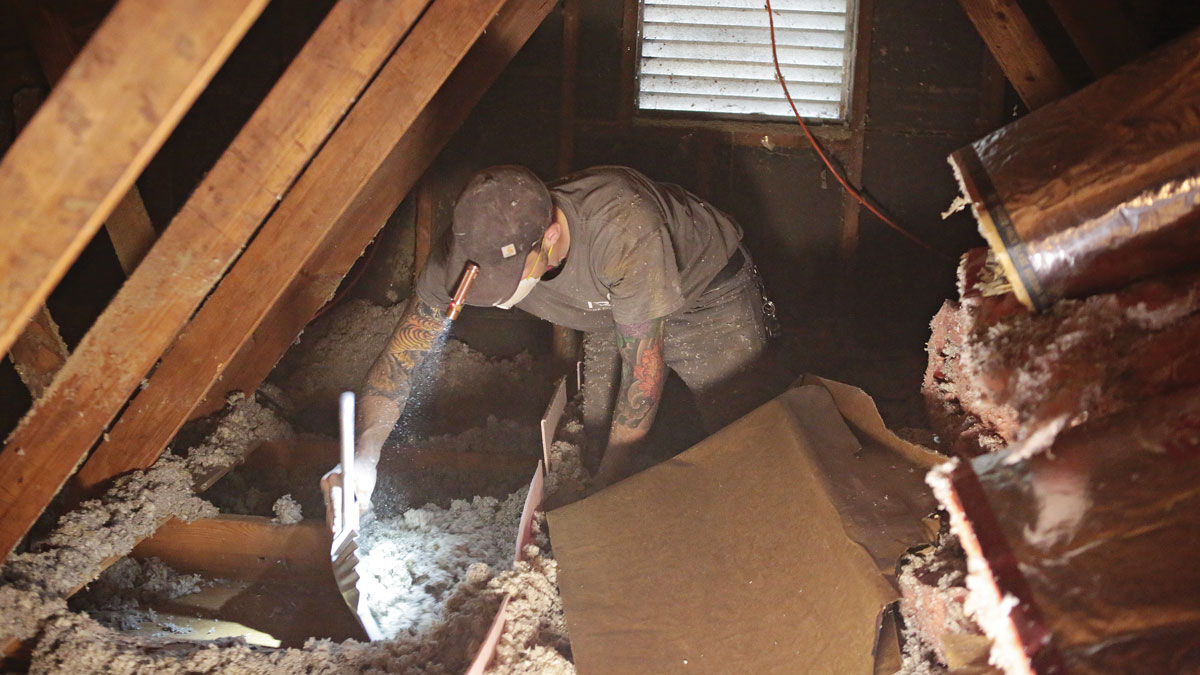 Worker cleaning attic of insulation material
